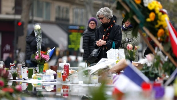 People gather in front of a makeshift memorial in Place de la Republique square in Paris, on Nov. 27, 2015, for a tribute to the 130 people killed in the Nov. 13 Paris attacks. Morocco says it has arrested a Belgian national linked to the Paris attackers.