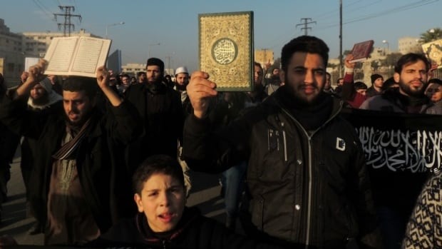 Men hold Koran holy book as they demonstrate outside the offices of the Al-Qaeda-linked Islamic State of Iraq and the Levant (ISIS) demanding that they stop fighting with the rebels on January 6, 2014 in the northern Syrian city of Aleppo.