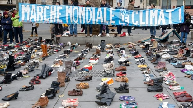 A banner which reads 'Global Climate March' is displayed in front of pairs of shoes symbolically placed on the Place de la République on Sunday. Thousands of activists took to the streets of Paris ahead of climate summit, despite a ban on public demonstrations following the Nov. 13 attacks.