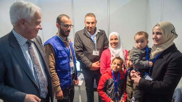 Minister of Immigration, Refugees and Citizenship John McCallum chats with members of a Syrian refugee family being interviewed by authorities in hope of being approved for passage to Canada at a refugee processing centre in Amman, Jordan, on Sunday, Nov. 29, 2015.