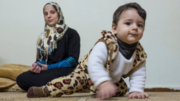 One-year-old Mohammad Mnaahe crawls away from his mother Wessam in the family's apartment on Nov. 30, 2015 in Irbid, Jordan. The Syrian refugee family is waiting for approval to immigrate to Canada.
