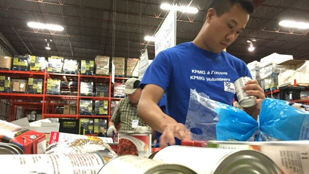 A volunteer sorts through donations at the Calgary Food Bank.