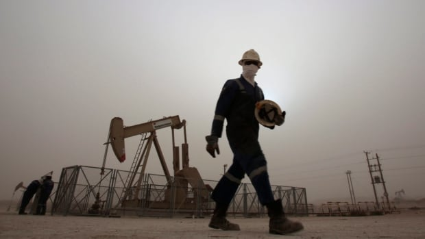 An oil worker walks by an oil pump. Oil and gas companies have slashed jobs this year and there may be more cuts in 2016.