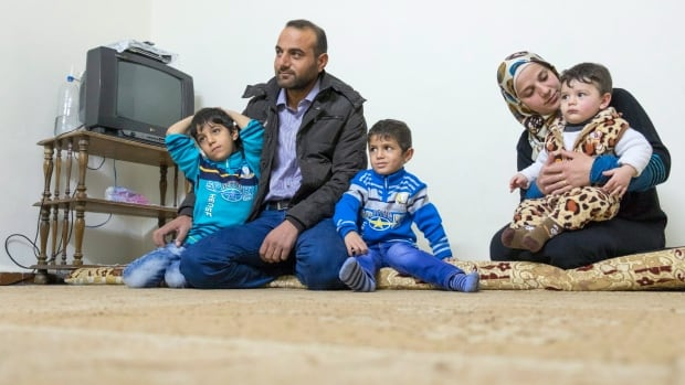 Mjdi Mnaahe, his wife Wessam and their sons Tamim, 6, Saif, 4 and Mohammad, 1, sit in their apartment Monday, November 30, 2015 in Irbid, Jordan. The Syrian refugee family hopes to come to Canada.