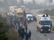 Migrants walk towards an official meeting point set by French authorities as part of the full evacuation of the camp in Calais on October 24, 2016.