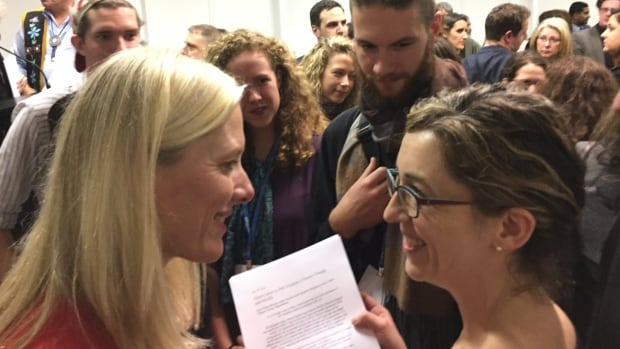 Courtney Howard, right, presents a letter on behalf of more than 150 Canadian doctors and medical students to Catherine McKenna, Canada's minister of Environment and Climate Change at the COP 21 conference in Paris.