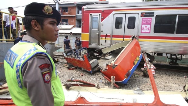 A police officer stands near the scene of an accident between a minibus and a commuter train at a railway crossing in West Jakarta on Dec. 6, 2015.