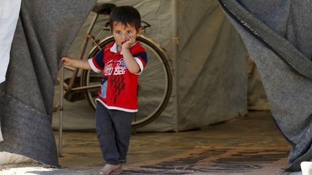 A Syrian refugee boy stands in front of his family's tent in the Al Zaatari refugee camp in the Jordanian city of Mafraq, near the border with Syria on Nov. 29, 2015.