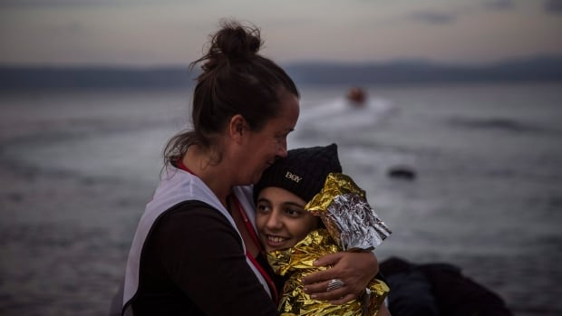 A volunteer hugs a girl on a beach on the Greek island of Lesbos with other refugees and migrants, on Nov. 24, 2015. Turkey's state-run news agency reported that 6 children drowned Tuesday while attempting a similar transit.