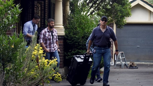 Australian officers come out of after a search of a home in Sydney's north shore early on Dec. 9. Australian Federal Police raided the Sydney home on Wednesday of the man named by Wired magazine as the probable creator of cryptocurrency bitcoin.