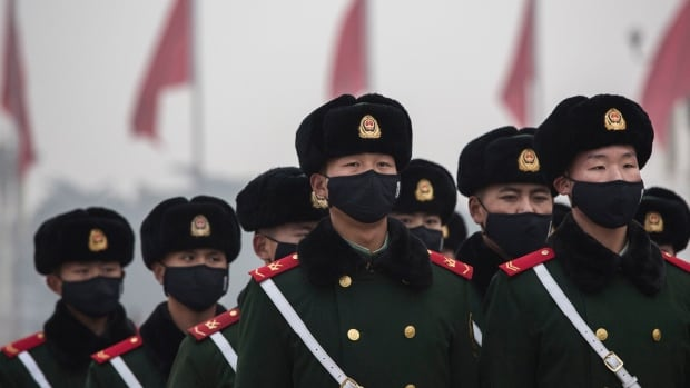 Chinese paramilitary police wear masks as they march through smog in Tiananmen Square on Dec. 9, in Beijing, China. The Beijing government issued a red alert for the first time since new standards were introduced earlier this year as the city and many parts of northern China were shrouded in heavy pollution.