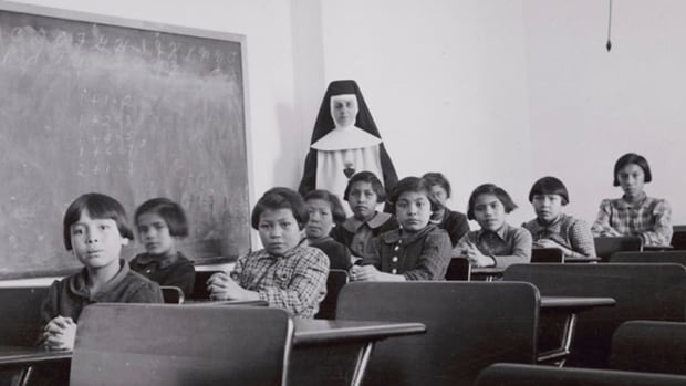 A group of students and a nun pose in a classroom at Cross Lake Indian Residential School in Cross Lake, Man., in February 1940. The Catholic Church ran more than half of Canada's residential schools, which devastated First Nations families and culture.