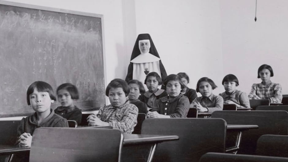 A group of students and a nun pose in a classroom at Cross Lake Indian Residential School in Cross Lake, Manitoba in February 1940.