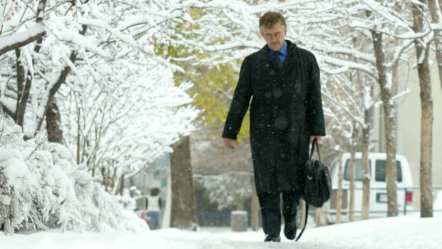 A businessman walks in a snowy downtown Calgary.
