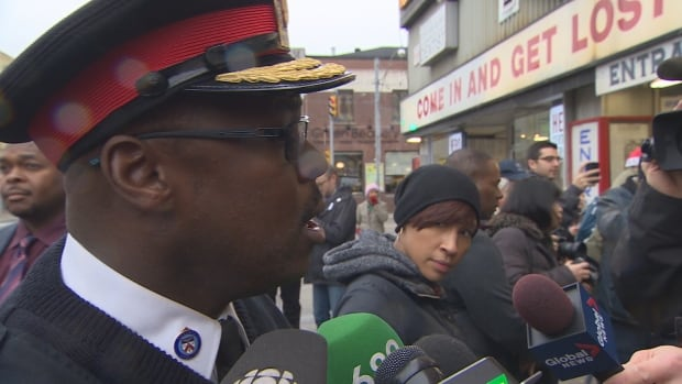 Toronto police Chief Mark Saunders speaks to reporters at the annual turkey giveaway at Honest Ed's on Sunday.