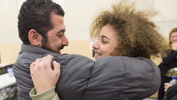 Newly arrived Syrian refugee Laila Beylouneh, right, is hugged her uncle Anas Fransis as they are reunited at a welcome centre, in Montreal, on Saturday. The family, originally from Aleppo, has been reunited after eight years.
