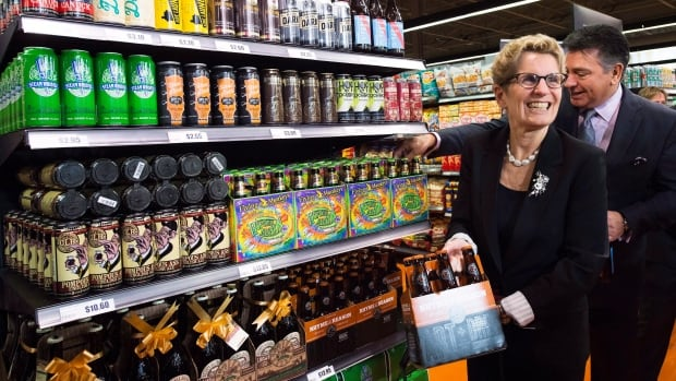 Ontario Premier Kathleen Wynne, seen here buying some beer, could announce the sale of Ontario wine in some grocery stores Thursday morning in Toronto.