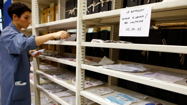 Archivist Mathilde Puntault puts up for drying some drawings from the Bataclan on shelves at the Paris Archives.