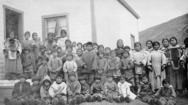 A group of Inuit women and children stand outside the school at the Pangnirtung Federal Hostel in 1927. The Indian Residential Schools Truth and Reconciliation Commission's final report was released on Tuesday.