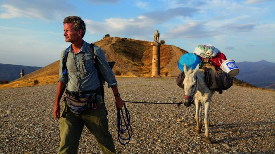 In eastern Turkey, Paul Salopek leads his mule past the Karakuş royal tomb, built in the first century B.C. by one of the area's many ruling states. When Syrians began to pour over the border 70 miles to the south, he and photographer John Stanmeyer drove down separately to report on the situation.