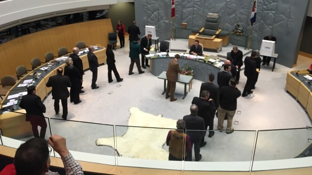 N.W.T. MLAs line up to cast their secret ballots for premier in the legislative assembly chamber on Wednesday.