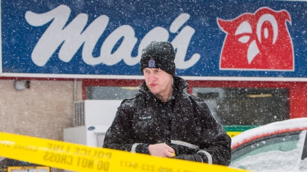 A police officer removes crime scene tape at a convenience store where one of the deadly shootings took place Friday.