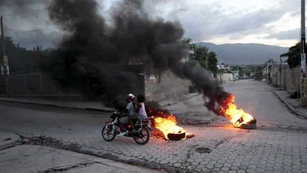 A motorbike passes burning tires at a barricade during protests after the announcement of the results of the presidential election, in this photo taken on Nov. 5 in Port-au-Prince. The long-running protests turned violent on Saturday.