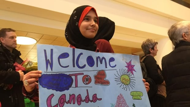 Wafaa Abukhousa, 12, of Altona, Man., holds a sign written in Arabic and English to welcome Syrian families.