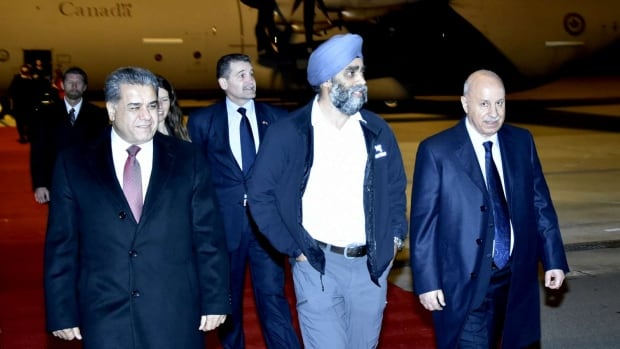 Canadian Defence Minister Harjit Sajjan walks with Kurdish Interior Minister Karim Sinjari, right, and Kurdish Foreign Minister Falah Mustafa Bakir, left, after arriving in Erbil in northern Iraq.