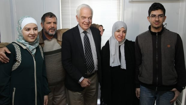 Immigration Minisiter John McCallum, centre, poses with Syrian refugees destined for Canada. McCallum says some cities need time to find housing for refugees before accepting more.