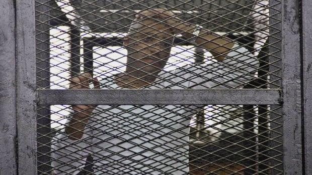 Mohammed Fahmy appears in a defendant's cage during a trial on terror charges in Cairo, Egypt, in May 2014. His case highlights the flaws in current legislation, Reis Pagtakhan says.