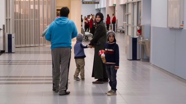 Members of a family of Syrian refugees look back at the arrival hall at the Welcome Centre at Toronto's Pearson Airport before boarding a bus to take them to a hotel as they land in Canada on Friday December 18, 2015. THE CANADIAN PRESS/Chris Young
