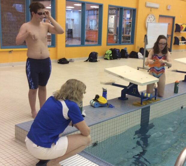 Coach Edie Rogers on pool deck with para-swimmers