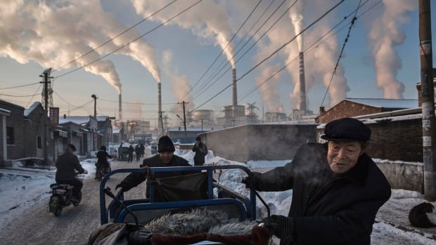 Men pull a motorized tricycle in a neighbourhood of Shanxi, China, that's next to a coal-fired power plant. China emits about a fifth of the world's greenhouse gases.