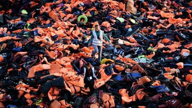 Volunteers walk on a pile of lifejackets left behind by migrants, many of whom seeking refuge in Western Europe, who arrived by boat on the Greek island of Lesbos on Dec. 3, 2015.