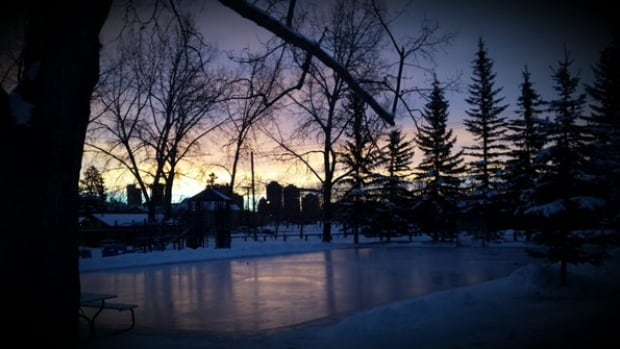 The sun rises over the backyard rink behind the CBC building in West Hillhurst.
