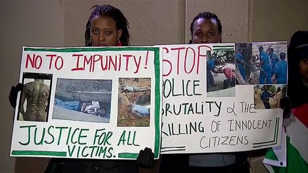 Two women hold up signs protesting the escalating violence in their central African homeland of Burundi at a candlelight vigil held Monday night outside the Calgary Courts Centre.