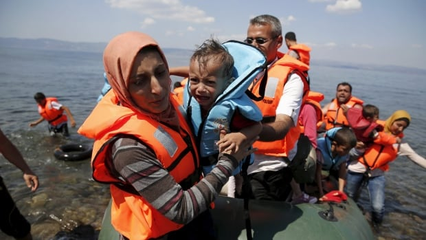 A Syrian refugee carries her baby as she arrives with other Syrian refugees on a dinghy on the island of Lesbos, Greece, during August last year. Online comment sections on news stories about Syrian refugees have been flooded with hateful messages.