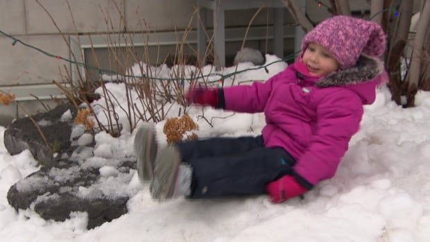 A young girl slides down a pile of snow delivered to Roger's House to give sick kids a white Christmas.