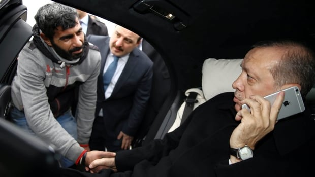 Turkish President Recep Tayyip Erdogan, right, takes Vezir Cakras by hand while inside his car stationed over the Bosporus Bridge in Istanbul on Friday. Erdogan's office says the Turkish president has talked Cakras out of jumping off a bridge to commit suicide.