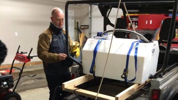 Scott Roessler puts the finishing touches on his homemade ice machine.