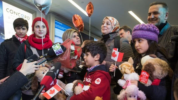 Tima Kurdi, third from left, stands with her brother Mohammad Kurdi, top right, upon arrival at the Vancouver airport. Pictured from left to right are Shergo Kurdi, 15, Haveen Kurdi, 16, Sherwan Kurdi, five months, being held by Tima, Rezan Kurdi, 8, their mom, Ghousun Kurdi, and Ranim Kurdi, front right, 10.