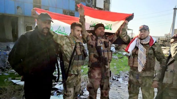 Iraqi soldiers hold national flags after retaking the government complex in central Ramadi,on Monday.