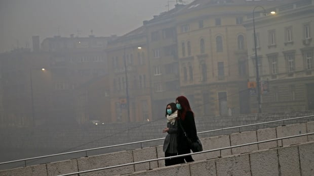 Women wearing masks walk as smog blankets Sarajevo on Dec. 23.