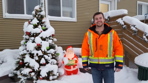 Peter Houweling, superintendent for Yellowknife's solid waste facility, poses with a Christmas tree salvaged from the dump. Houweling says he's seen an increase in consumer awareness of the waste they're producing, even when shopping at the grocery store.