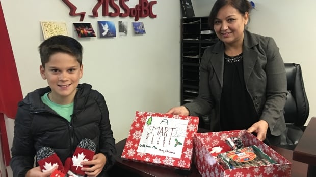 Max Honey delivers Olympic mittens to the Immigrant Services Society each week. Shamsia Alef-Sultani works at ISS of BC and looks forward to his weekly visit.