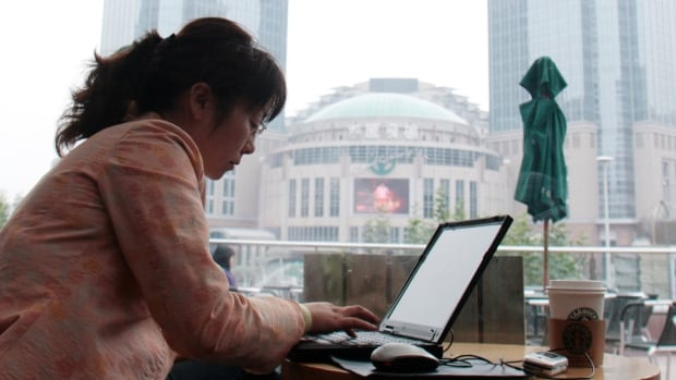 A woman works on her laptop in a coffee shop. Scenese like this could become more common as office work becomes increasingly decentralized.