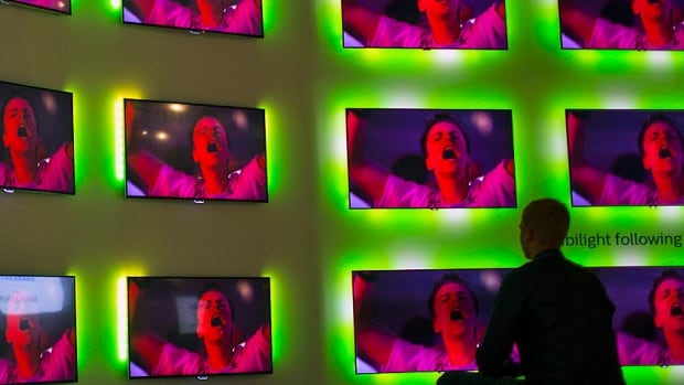 A man sits in front of Philips ambient light flatscreens at the consumer electronics trade fair in Berlin in September. Next-generation 4K TVs, with extra features like the ability to absorb a room's ambient light, will be front and centre in Vegas this week.
