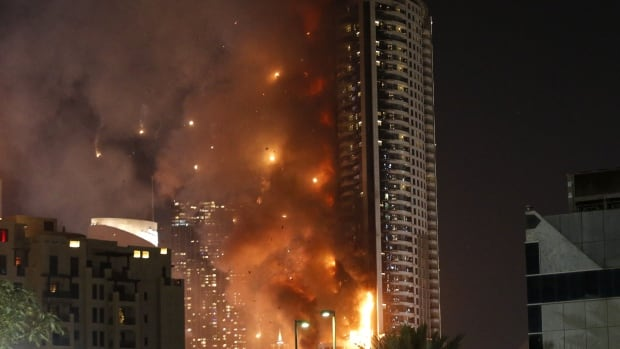 Flames rip through the Address Downtown hotel after it was hit by a massive fire, near the world's tallest tower, Burj Khalifa, in Dubai, on December 31, 2015.