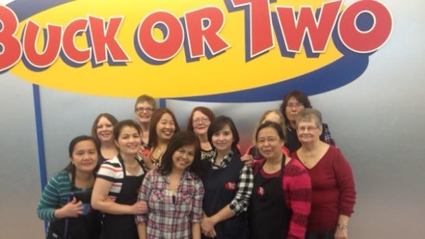 Darlene Appleyard (back row, centre) smiles with her employees in front of the Buck or Two in Portage Place Shopping Centre on Dec. 31, 2015.